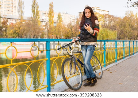 Young woman checking for text messages on her mobile phone as she stands holding her bicycle on a promenade above an urban canal or lake