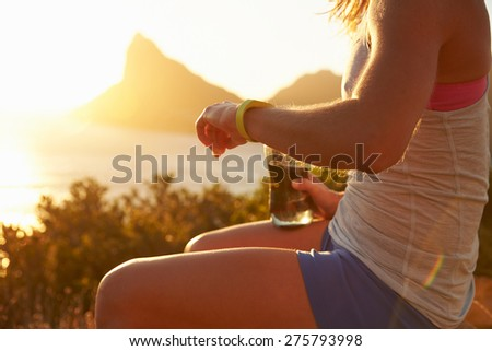 Young woman checking her sports watch - stock photo