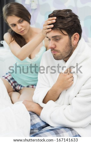 Young woman checking man's temperature on bed
