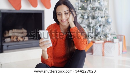 Young woman checking out her text messages on her mobile phone as she sits cross-legged on the floor in front of the Christmas tree at home.