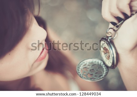 young woman checking time on a pocket watch