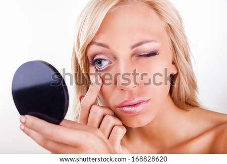 Young woman checks a contact lens in her eye - stock photo
