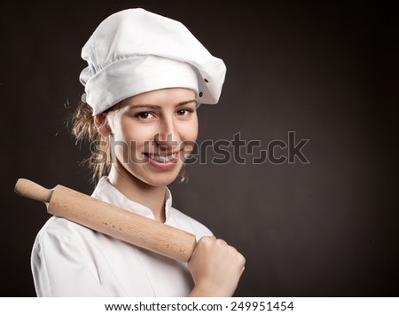 young woman chef holding a rolling pin - stock photo