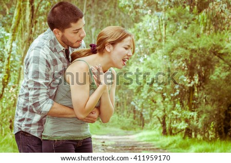 Young woman choking with man standing behind performing heimlich maneuver, park environment and casual clothes