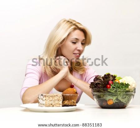 Young woman chooses between  a salad and baking - stock photo
