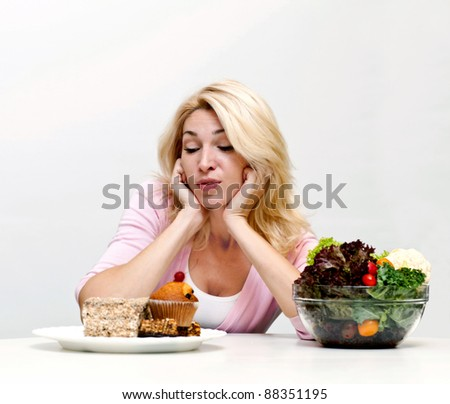 Young woman chooses between  a salad and baking - stock photo