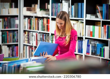 Young woman choosing a book in a library - stock photo