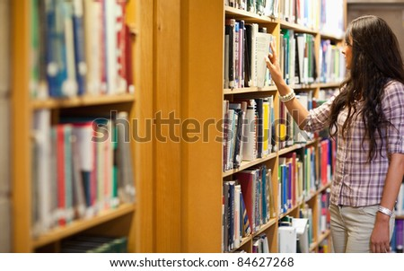 Young woman choosing a book in a library