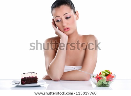 Young woman choosing between cake and healthy salad - stock photo