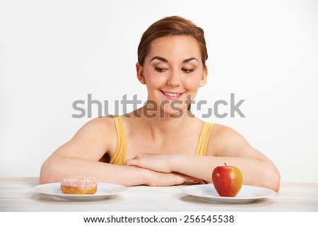 Young Woman Choosing Between Dounut And Cake For Snack - stock photo