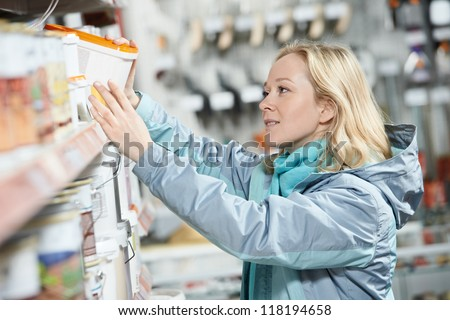 Young woman choosing color paint during hardware shopping in home improvement store supermarket - stock photo