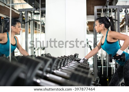 Young woman choosing dumbbells in gym. She stay near a mirror and see her reflection. - stock photo