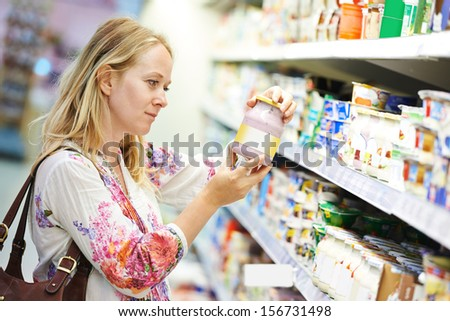 Young woman choosing fresh milk produces at shopping in dairy supermarket store - stock photo