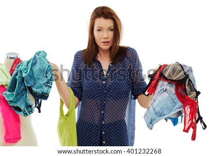 Young woman choosing from different clothes, isolated over white background - stock photo