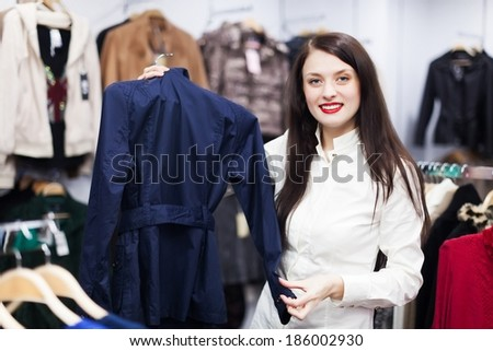 Young woman choosing jacket at boutique - stock photo