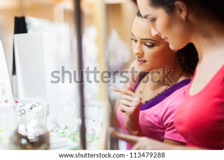 young woman choosing jewelery in shop - stock photo