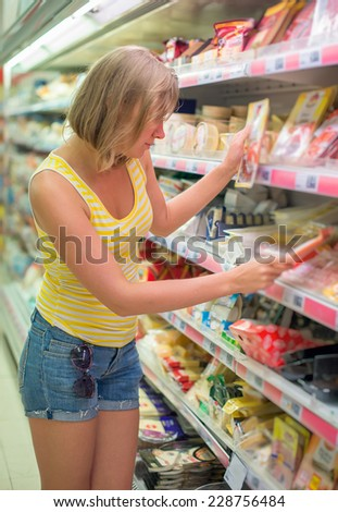 Young woman choosing meat in grocery store. - stock photo