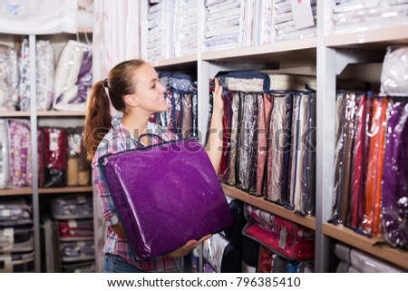 Young woman choosing new bed linen for home in textile shop