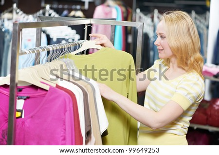 Young woman choosing sweater and blouse during clothing shopping at store