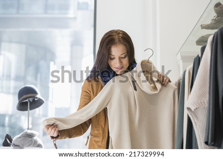 Young woman choosing sweater in store - stock photo