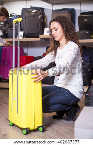 Young woman choosing travel suitcase in haberdashery shop