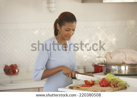 Young woman chopping vegetables - stock photo