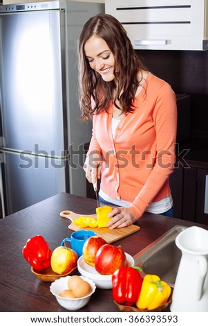 Young woman chopping yellow  pepper in kitchen