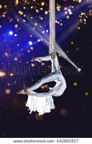 Young woman circus air gymnast. On illumination background