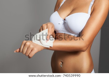 Young woman clean hands with wet wipes, body breast lingerie panties in blurred background