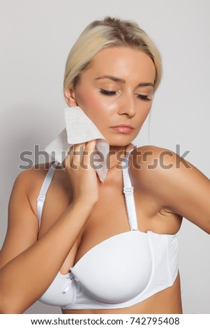 Young woman clean neck with wet wipes, body breast lingerie