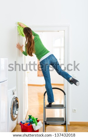 Young woman cleaning at home, she has a cleaning day and using a duster or dust cloth - stock photo