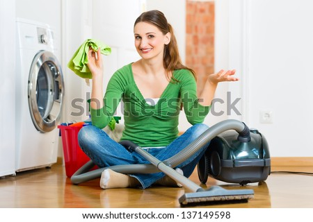 Young woman cleaning at home, she has a cleaning day and using a vacuum cleaner cleaning products and a bucket - stock photo