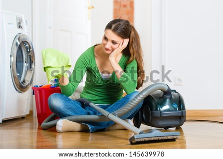 Young woman cleaning at home, she has a cleaning day and using a vacuum cleaner cleaning products and a bucket but she does not feel like it - stock photo