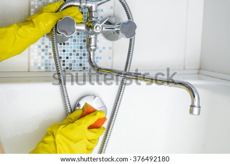 Young woman cleaning bathroom