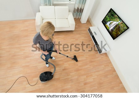 Young Woman Cleaning Floor With Vacuum Cleaner At Home - stock photo