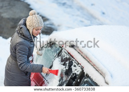 Young woman cleaning her car from snow and frost on a winter morning, she is freezing and needs to get to work - stock photo
