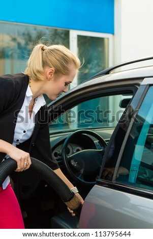 Young woman cleaning her car with a vacuum cleaner