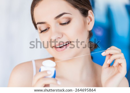 Young woman cleaning her teeth with dental floss - stock photo