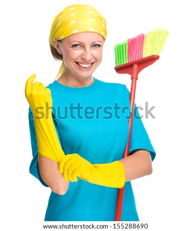 Young woman - cleaning maid holding broom and putting on yellow gloves, isolated over white - stock photo