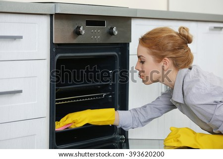 Young woman cleaning oven at the kitchen