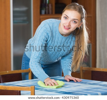 Young woman cleaning table in living room and smiling