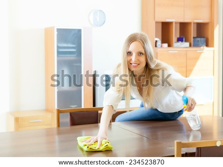 young woman cleaning  table with rag and cleanser at home