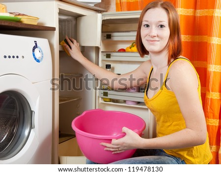 Young woman  cleaning the refrigerator at her kitchen