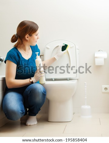 Young woman cleaning toilet bowl with sponge in bathroom at home