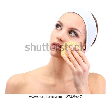 Young woman cleansing her face, isolated on white