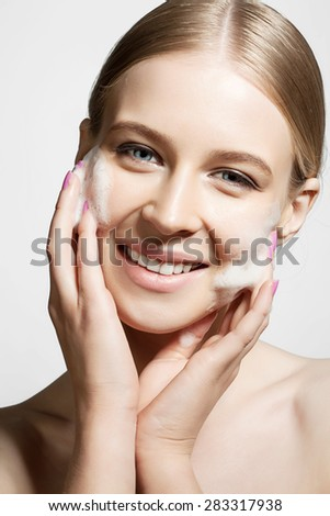 Young woman clears a face skin foam on a white background - stock photo