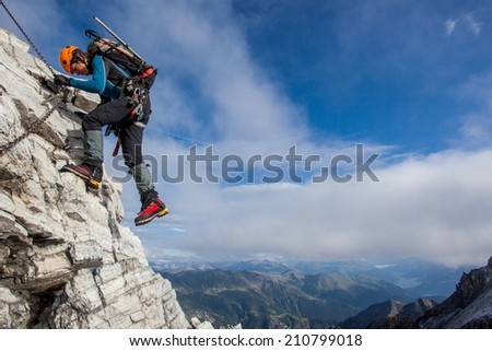 Young woman climbing along the fixed rope high above mountain valley - stock photo