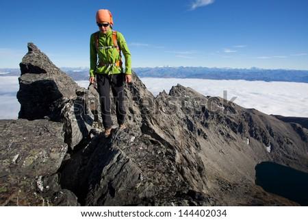 Young woman climbing exposed alpine ridge - stock photo