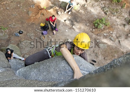 Young woman climbing on a wall, rock climbing in mountains with natural background. - stock photo