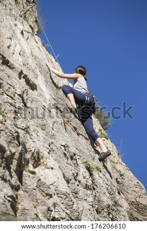 Young woman climbing. Rock climber. - stock photo